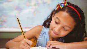 Menina escrevendo de lápis no caderno. Ao fundo, há um mapa-múndi.