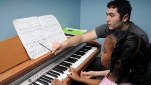 Menina toca piano enquanto é orientada por professor de música. Acima do piano, há uma partitura sendo lida pela menina.