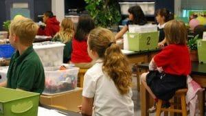 Foto de uma sala de aula mostrando diversos alunos de costas sentados em carteiras olhando para o quadro negro. Nas carteiras, estão caixas repletas de materiais.