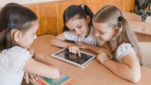 Três meninas brincam com um tablet, sentadas à mesa.