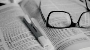 Óculos e marca-texto em cima de livro.