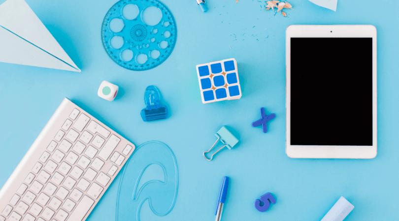 Uma série de materiais escolares (caneta, borracha, régua) estão dispostos numa mesa junto a um tablet. Todos os materiais exceto o tablet são azuis.