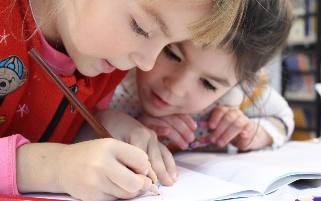 Alfabetização e letramento representadas em foto de meninas pequenas escrevendo e estudando juntas. Imagem de klimkin por Pixabay