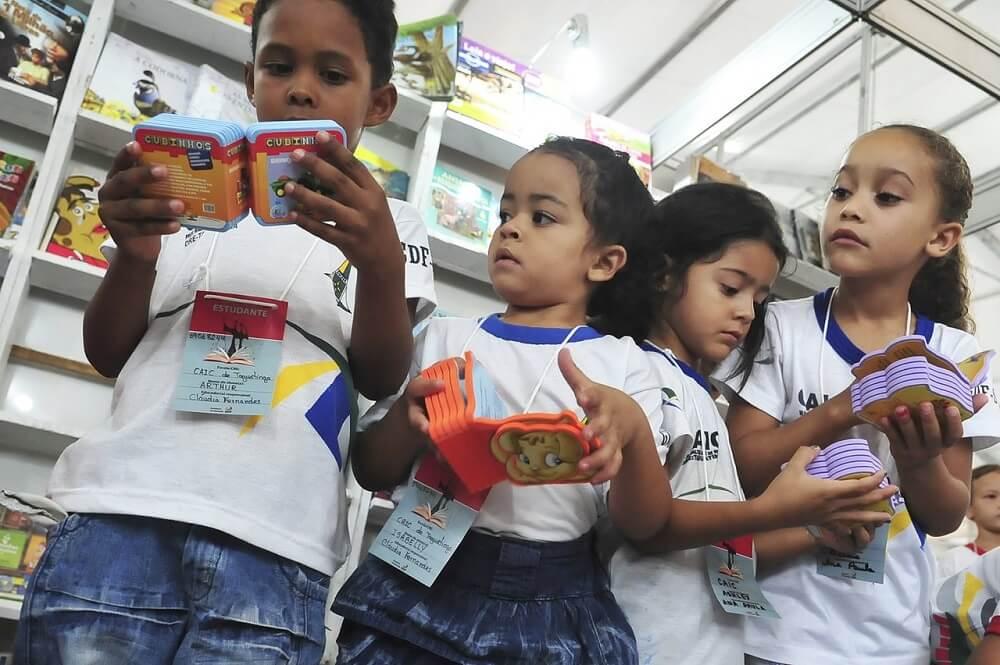 Progressão automática, exclusão escolar oculta são duas das principais causas do baixo nível de aprendizado na alfabetização. Na foto, crianças leem livros infantis. Crédito: Agência Brasil.