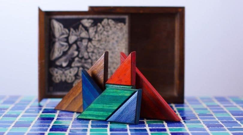 Peças de tangram dispostas na vertical sobre uma superfície de azulejos.