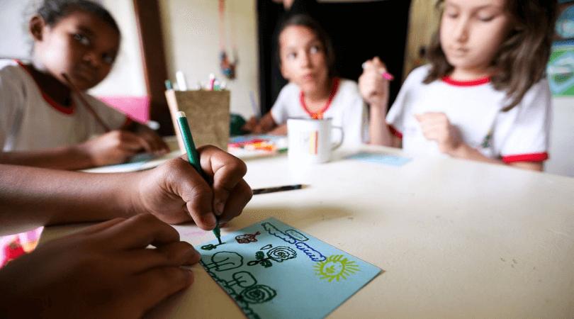 Foto de crianças em sala de aula, representando escolas que investem em uma boa alfabetização.